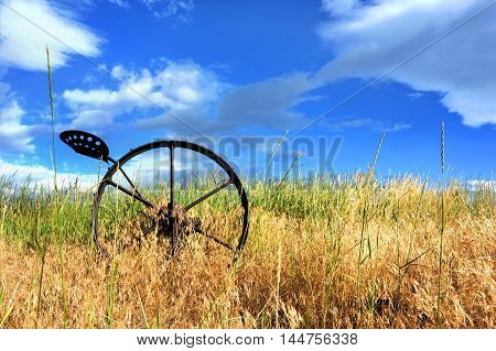 Antique horse drawn plow sits abandoned in a field in Hapy Valley Wyoming. Metal plow has seat and metal wheel with spokes.