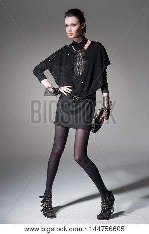 full-length,fashion model in modern clothes holding handbag posing