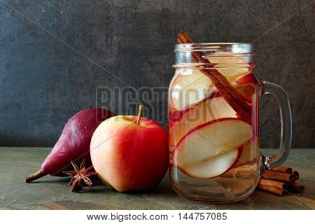 Autumn Themed Detox Water With Apple, Cinnamon And Red Pear In A Mason Jar On A Dark Slate Backgroun