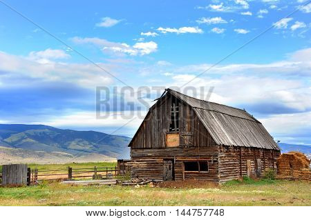Rustic log barn has wooden roof and is in disrepair. Field behind barn rolls across the distance to the mountains of Paradise Valley Wyoming.