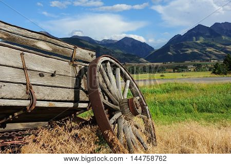 Broken down wagon is one of the few relics of the west. Wagon faces the mountains surrounding Paradise Valley in Montana. Weeds and grass grow around wagon.