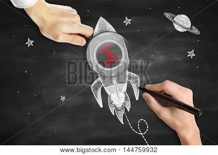 Male hands drawing and holding magnifier over rocket ship sketh with red dollar sign. Blackboard background. Start up concept
