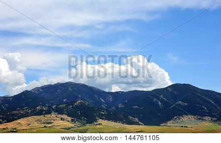 Bridger Mountain Range near Bozeman Montana is covered in trees and fluffy clouds.