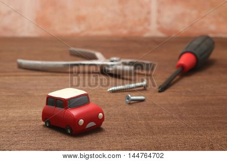 Miniature car and maintenance tools on wood.  Concept of car maintenance.