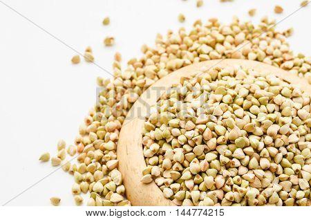 Uncooked buckwheat in wooden dish. premium buckwheat groats on white background