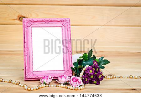 Blank pink vintage photo frame with flower on wooden background Saved clipping path.