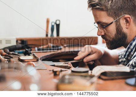 Jeweler sitting at a bench in his workshop using a file to shape and smooth out a silver ring