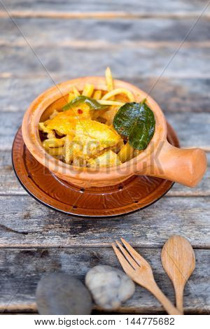 Thai food curry streaky pork with bamboo shoots in earthenware on wood