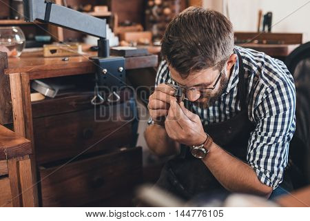 Jeweler using a loupe to examine a gem he is working with while sitting at a bench in his workshop