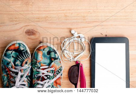 The Colorful Canvas Shoe, White Earphone With Sunglasses And Tablet On Wooden Background. Accessorie