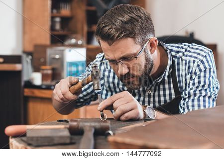 Focused jeweler in an apron using a hammer to shape a new ring while working at a bench in his workshop