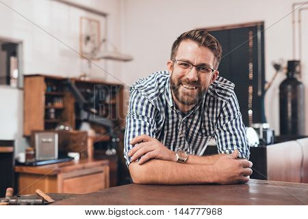 Portrait of a smiling young jeweler leaning on a bench in a workshop full of tools and jewelry making equipment