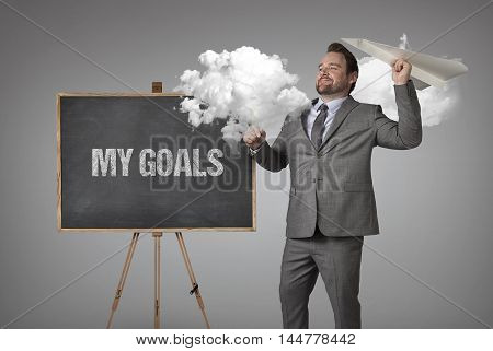 My goals text on blackboard with businessman and paper plane