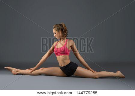 Aerobics. Studio photo of slim girl doing gymnastic split