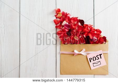 Cute post message with flower petals, copy space. Floral composition of rose bloom and kraft paper on white wooden background, romantic present, flat lay