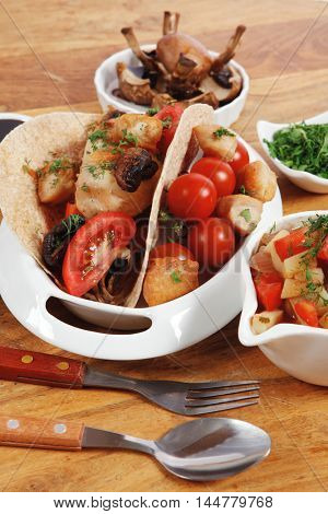 big mexican taco served with soup, fresh vegetables , baked mushroom with teriyaki sauce , on white crockery plates over wooden table with green staff