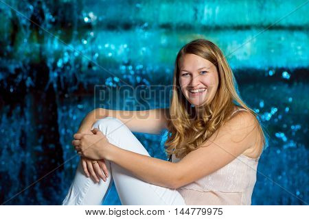 A teenage girl poses in front of a blue waterfall she is slightly nervous and is pulling her chin back as she smiles.