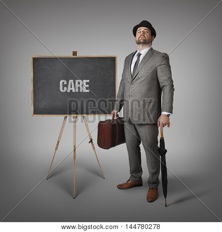 Care text on  blackboard with businessman holding umbrella and suitcase