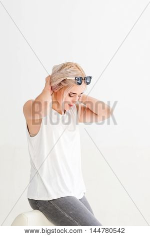 Beautiful sitting blonde model touching her hair. Young attractive woman looking down with hands raised to her head, white background, free space.