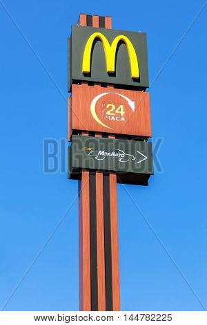 TVER REGION, RUSSIA - JUNE 26 2016: McDonald's logo on a pole against the blue sky. McDonald's is the world's largest chain of hamburger fast food restaurants