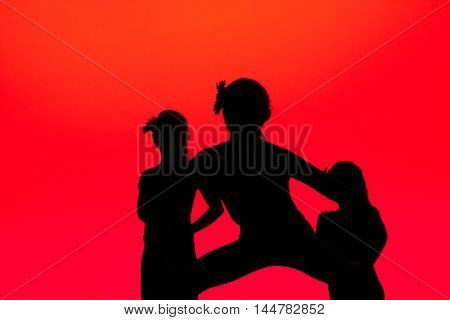 dancers strike a pose silhouetted against a red background