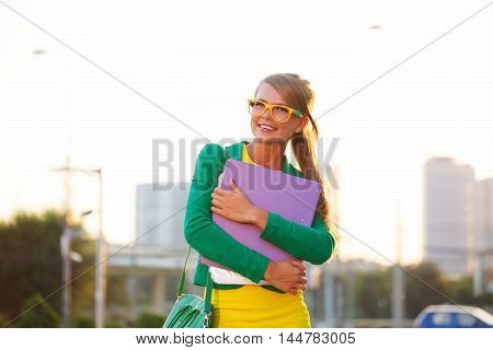 Business girl with directory in her hands. Girl in glasses and jacket smiles and looks away.
