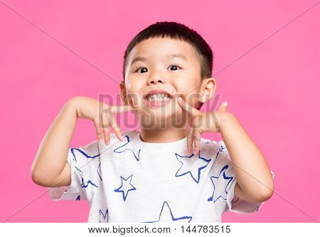 Little boy putting finger on cheek