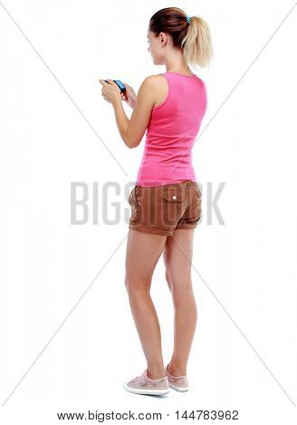 back view of standing young beautiful woman and using a mobile phone. Isolated over white background. Sport blond in brown shorts watching footage on a compact camera.