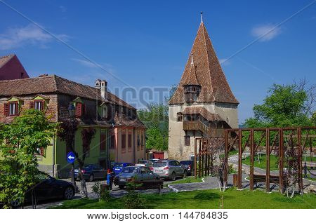 Sighisoara, Romania - May 2, 2014: Shoemakers tower (Turnul Cizmarilor) part of Sighisoara fortress and medieval houses of old town. Transylvania Romania