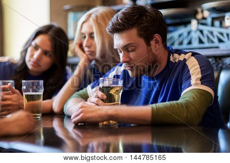 people, leisure, soccer and sport concept - unhappy football fans or friends with beer at bar or pub