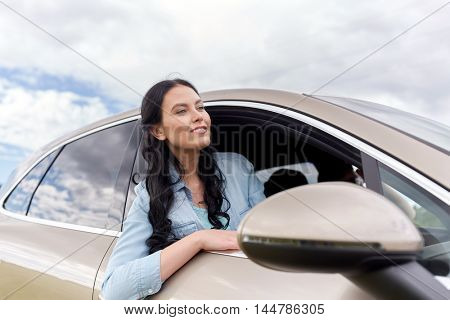 summer vacation, holidays, travel, road trip and people concept - happy young woman driving in car