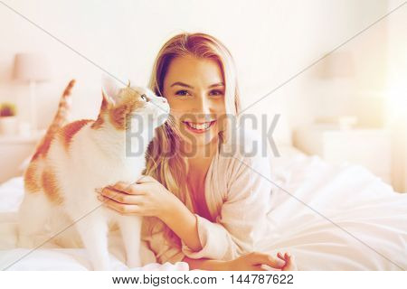 pets, morning, comfort, rest and people concept - happy young woman with cat in bed at home