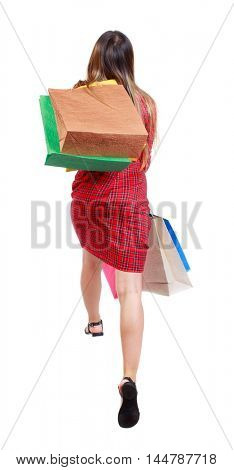 back view of a woman jumping with shopping bags. girl in red plaid dress jumping holding a gift paper bags.