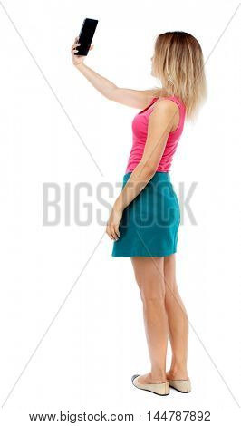 back view of standing young beautiful woman using a mobile phone. Isolated over white background. Blonde in a red sweater and green skirt makes selfie on the tablet.