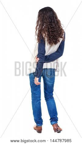 back view of standing young beautiful woman. Long-haired girl with curly hair standing with his hands behind his back.
