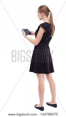 back view of standing young beautiful woman and using a mobile phone. girl watching. Isolated over white background. Blonde in a short black dress holding a tablet horizontally.
