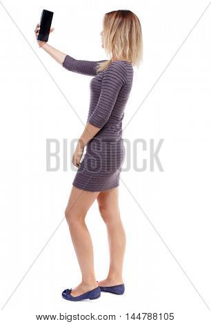 back view of standing young beautiful woman using a mobile phone. Isolated over white background. Blonde in violet short dress makes selfie on the tablet.