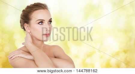 beauty, people and body care concept -beautiful young woman face and hands over yellow holidays lights background