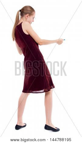 back view of standing girl pulling a rope from the top or cling to something. Isolated over white background. A girl in a burgundy dress pulling rope side.