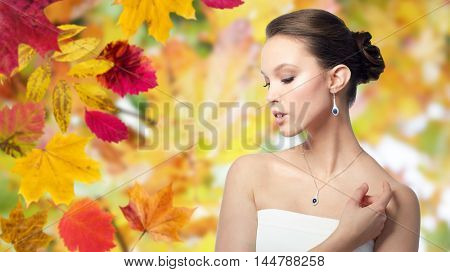 beauty, jewelry, wedding accessories, people and luxury concept - beautiful asian woman or bride with earring and pendant over autumn leaves background