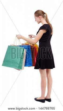 back view of woman with shopping bags. Isolated over white background. Blonde in a short black dress looks into colorful shopping bags.