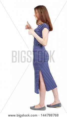 Back view of woman thumbs up. brunette in a blue striped dress is cancer and shows a thumbs-up sign of approval.