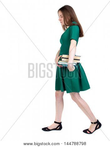 Girl comes with stack of books. side view. slender brunette in a green short dress sadly goes to the side with a pile of books.