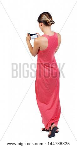 back view of standing young beautiful woman using a mobile phone. girl watching. slender woman in a long red dress is standing back and taking pictures on the phone.