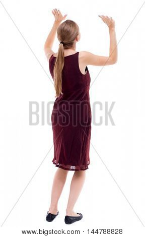 back view of woman protects hands from what is falling from above. Isolated over white background. A girl in a burgundy dress holding hands pushing something up.