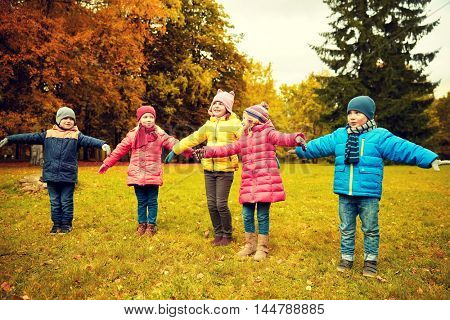 autumn, childhood, leisure and people concept - group of happy little children running and playing planes outdoors