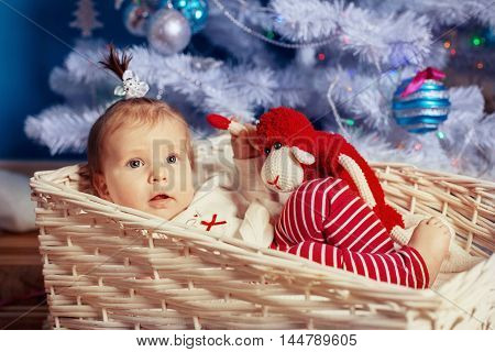 baby is a toy at tree. The concept of New Year and Christmas