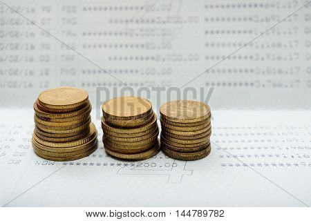 Stack of gold coins with account bank or bank book save money and save life