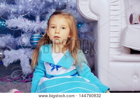 little girl in a dress near the tree. The concept of New Year and Christmas