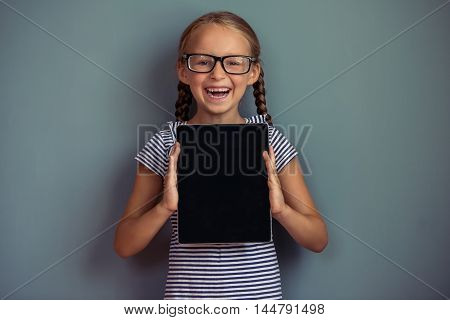 Cute little girl in dress and eyeglasses is showing a digital tablet looking at camera and smiling standing on gray background